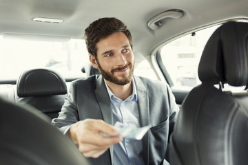 Man paying the taxi with the cash