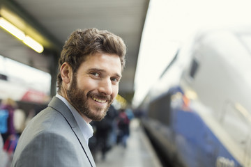 Portrait of cheerful man on platform station. Looking at camera