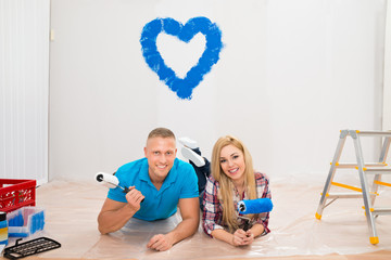 Couple With Paint Roller Lying On Floor