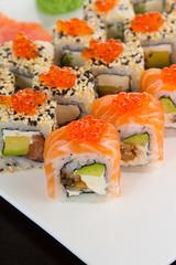 Japanese tasty sushi set on a white plate over black background