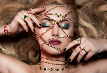 Art portrain of woman with glamout make up and fashion jewelry.