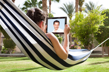 Woman In Hammock With Digital Tablet