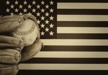 Worn baseball glove and used ball on American Flag
