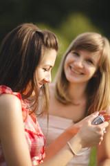 Young women having fun looking at photos on digital camera