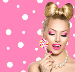 Beauty girl eating colourful lollipop over polka dots background