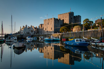 Sunrise at Castletown Harbor in the Isle of Man with Castle Rushen and boats reflecting in the water.