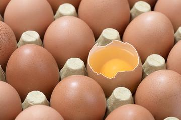 Cardboard egg box with one broken brown egg
