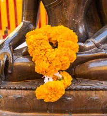 The marigold garland on hand of the ancient bronze image of budd