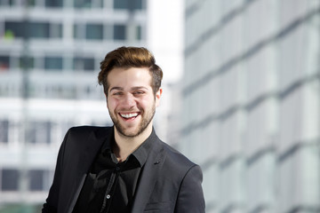 Attractive young man with beard smiling in the city