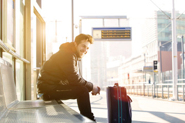 Happy young man waiting for train at station with bag