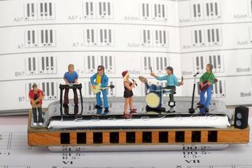 gruppo rock in miniatura mentre suona su un'armonica a bocca