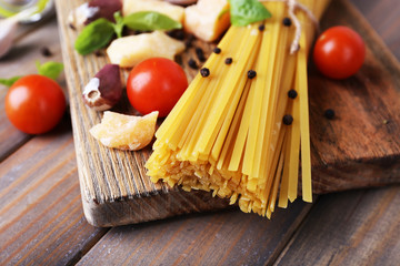 Raw pasta with cheese and vegetables on table close up