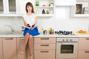 Young cheerful female sitting on the kitchen counter