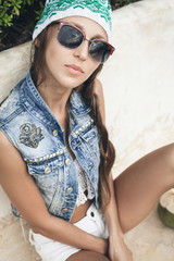 Woman in sunglasses and denim vest looking at the camera