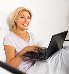 Smiling female with laptop laying