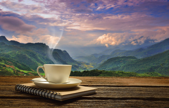 Morning cup of coffee with mountain background at sunrise