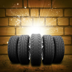 Car wheels. Background is brick wall, concrete floor and light