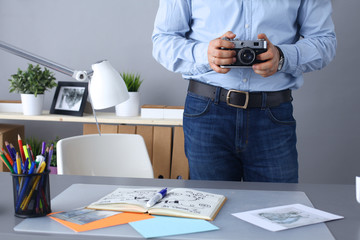Photographer processing pictures standing at the desk