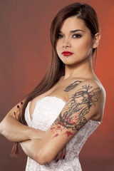 pretty young woman with tattoos posing in white corset