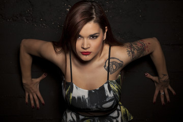 pretty young woman with tattoos posing in a dress on a black