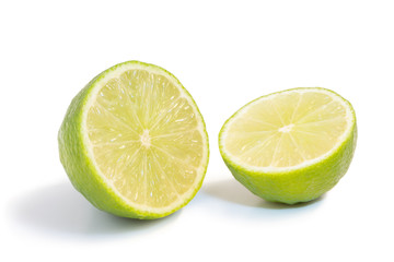 Closeup of a ripe lime fruit cut in half isolated on white