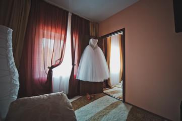 The wedding dress hangs in a room.