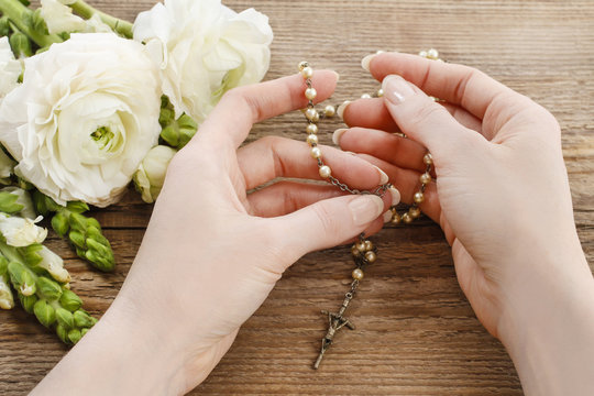Woman holding wooden rosary in hands.