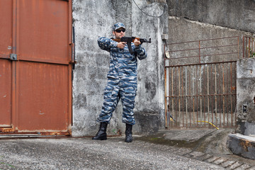 Caucasian military man in urban warfare protecting iron gate wit