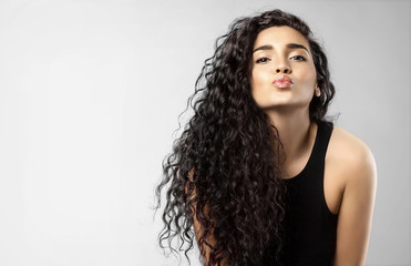Real woman with beauty black hair gives a kiss