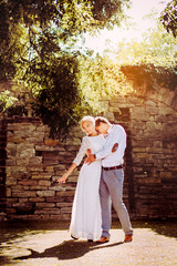 Loving couple dancing on stone wall background