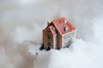 small house standing on snow