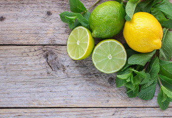 Juicy ripe citrus on an old wooden table - lime, lemon and mint