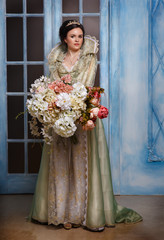 beautiful queen holding a large bouquet of flowers.