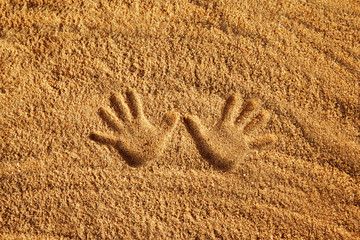 Close-up image of hand prints on yellow textured sand background