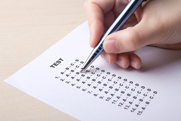 woman filling test sheet with answers