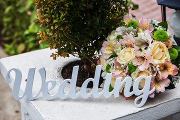 The word Wedding and bridal bouquet