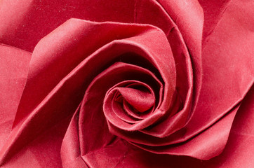 Abstract closeup of a romantic red paper origami rose flower