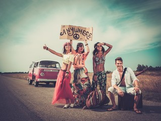 Multinational hippie hitchhikers on a road