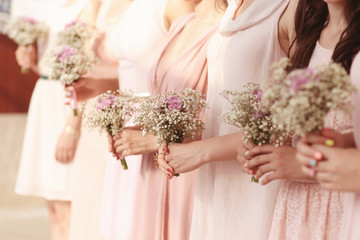 Hands of bridesmaid holding a beautiful gypsophila bouquet