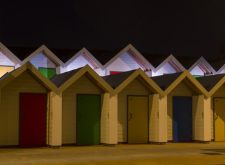 beach huts at night with colourful doors