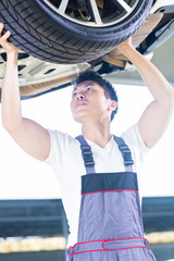 Asian Chinese car mechanic changing auto tire