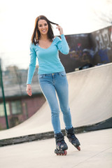 Beautiful young woman on rollerblades in a skateboard park