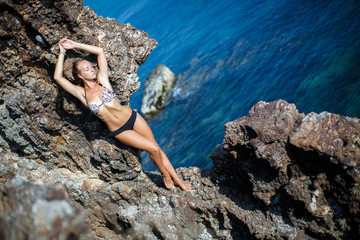 Girl standing on coastal sea rocks. Well being healthy lifestyle