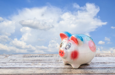 Piggy bank on wooden table over blue sky blurred background