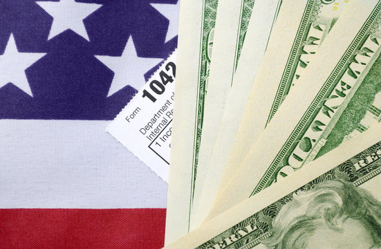 USA Tax Day concept with income tax form and cash on stars and s