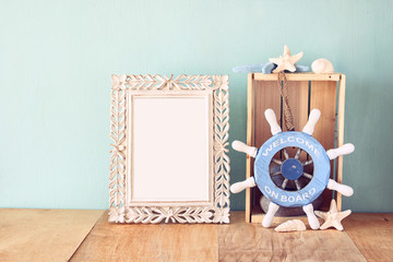 old vintage frame with naurical wheel on wooden table. vintage f