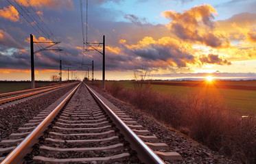 Photo sur Toile Voies ferrées Orange sunset in low clouds over railroad