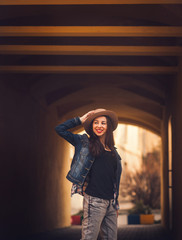portrait of a smiling girl in a hat outdoors in city