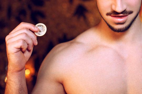 Sexy macho man holding condom closeup
