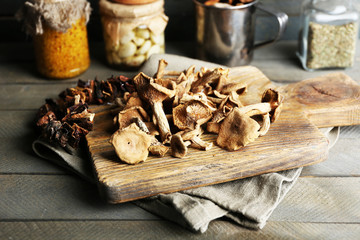 Dried mushrooms on cutting board on wooden background